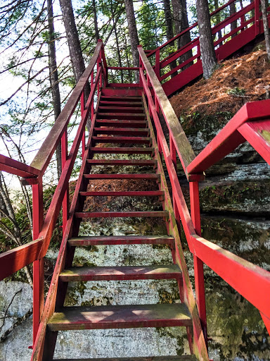 Red wooden stairs ascending sandstone escarpment