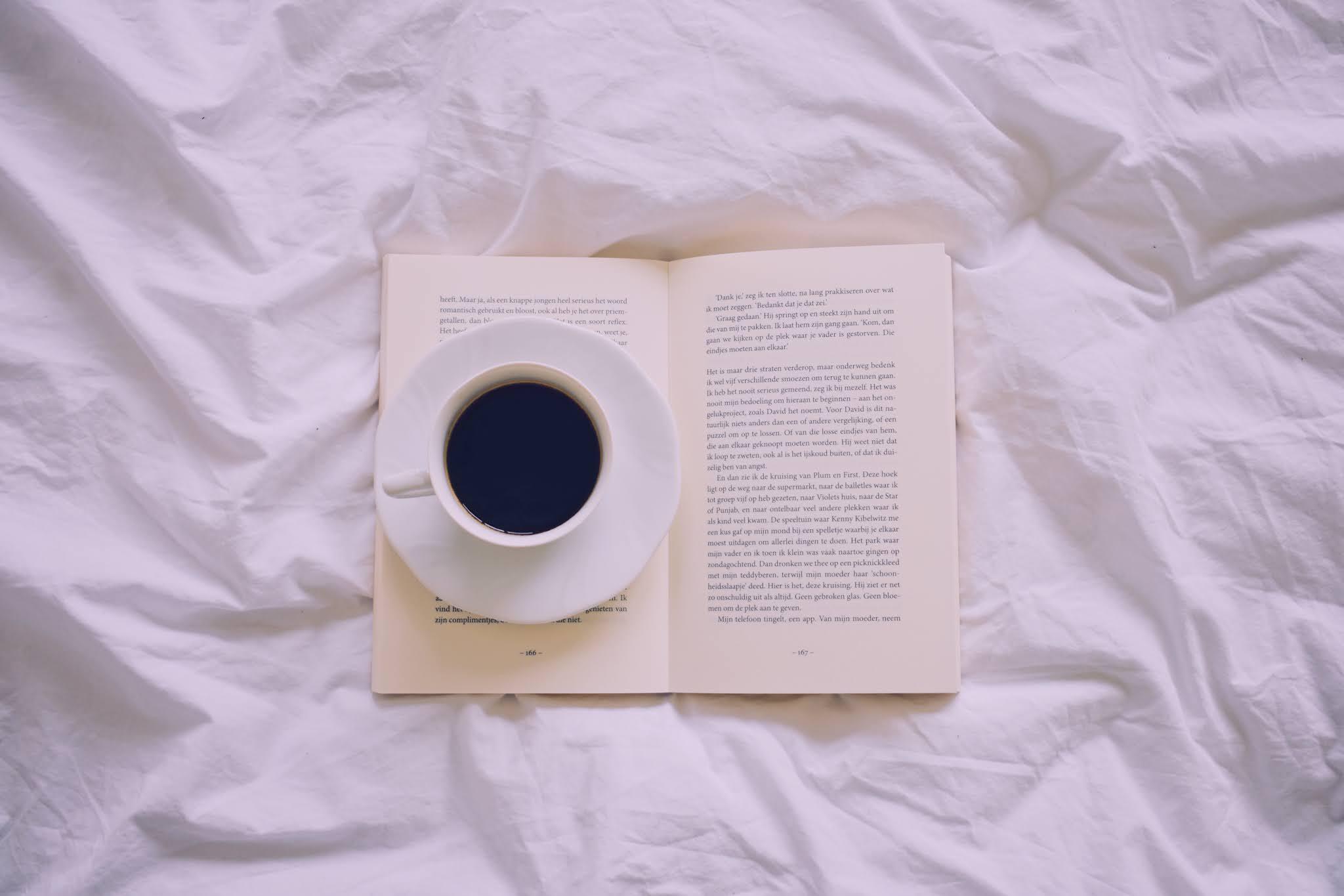 Opengeslagen boek op een wit laken met daarop een schoteltje en een tasje koffie.