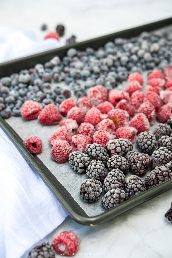 Frozen blackberries, raspberries, and blueberries on baking sheet