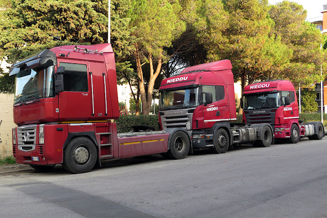 Three red trucks in Via Ferraris, Livorno