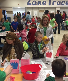 Group of children decorating bags with crowns