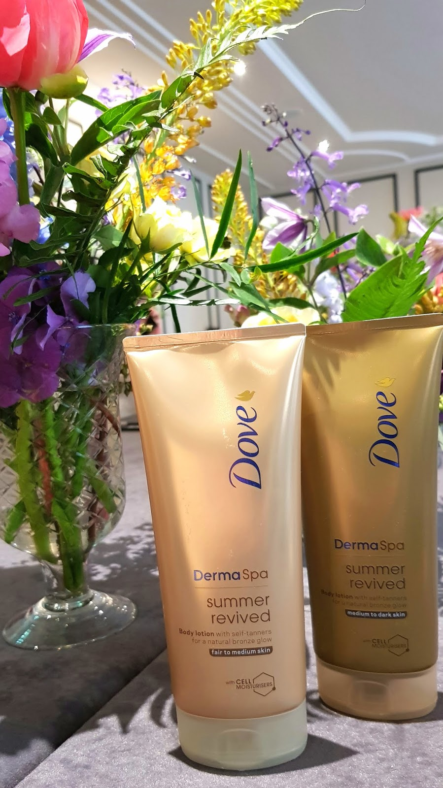 Dove DermaSpa Summer Revived gradual tanners next to beautiful summer flowers