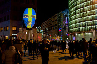 potsdamer platz. faces projected on a blank half-head on a wall during berlin's light festival oct 2011