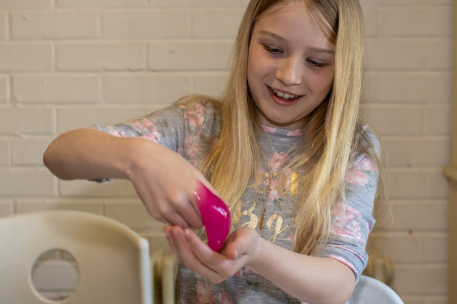 A girl holding pink runny slime in her hand and smiling
