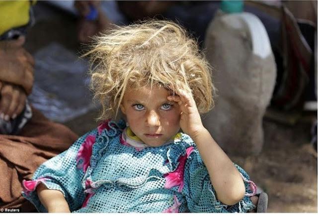 طفلة ايزيدية تجلس على الحدود العراقية السورية، بعد الفرار من تنظيم داعش، تنتظر العبور إلى محافظة دهوك بشمال العراق
