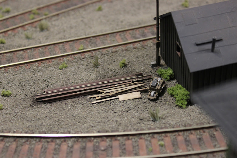 A scrap pile made from spare rail and basswood pieces behind a plastic shed kit in a gravel rail yard scene