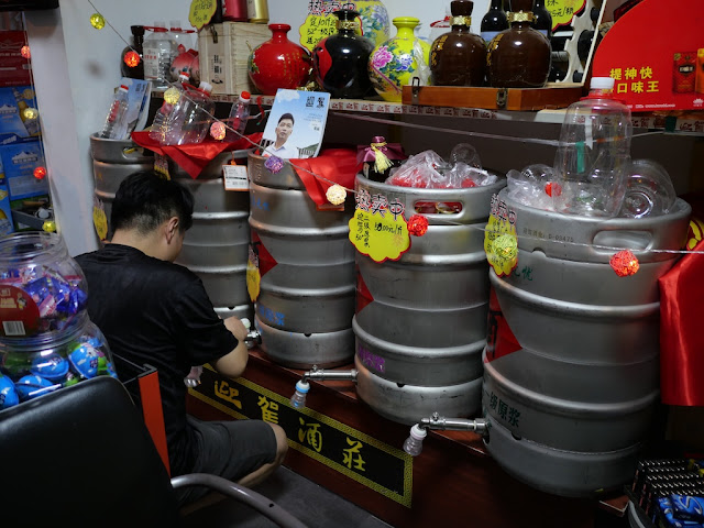 man pouring baijiu from a keg