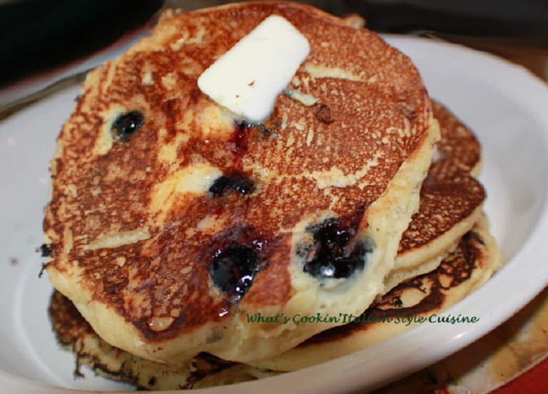 these are ricotta blueberry pancakes on a white plate with butter and maple syrup