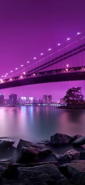 خلفية مساء ارجواني يخيم على جسر البحيرة المعلق