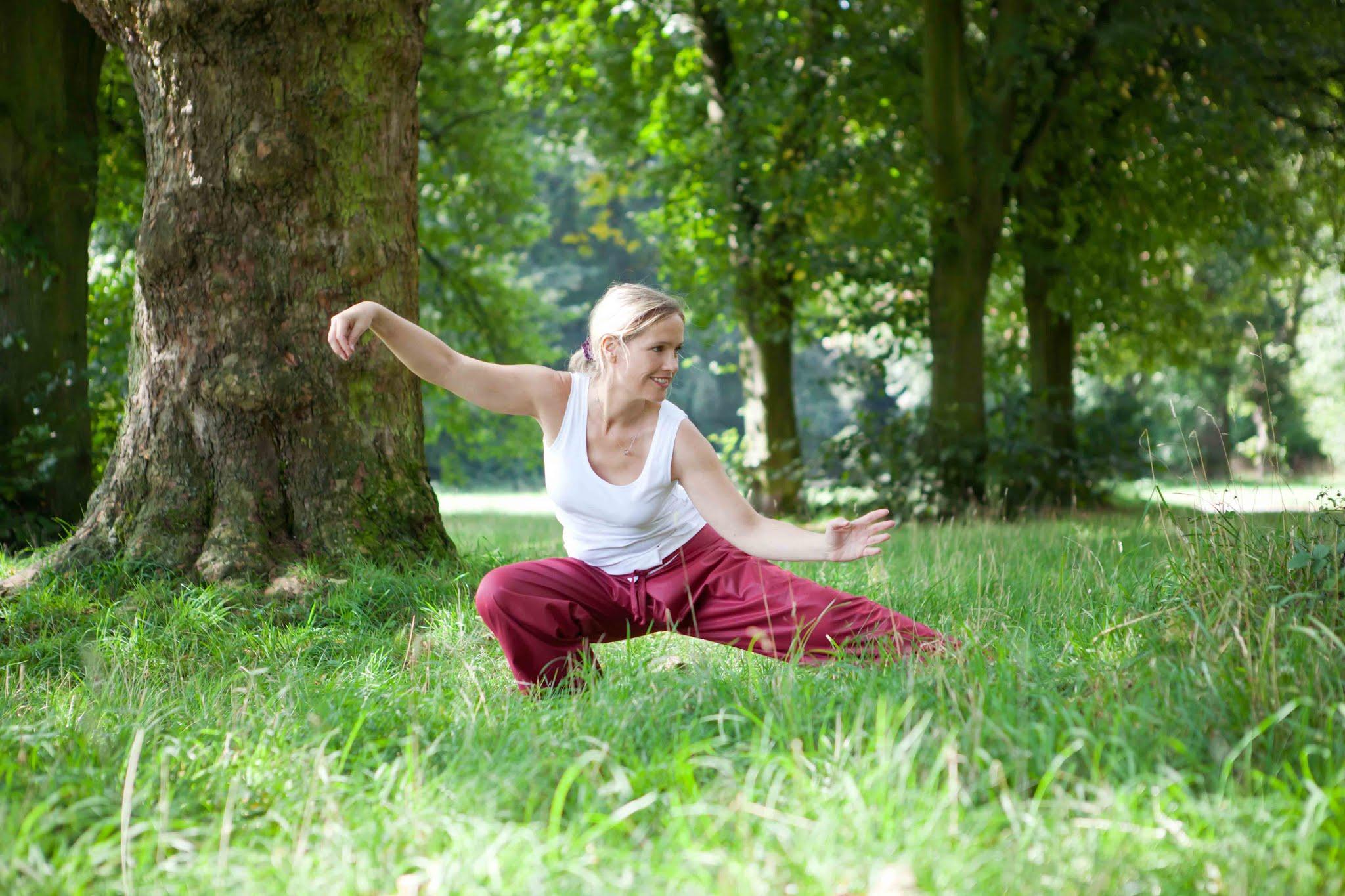 Frau in roter Hose und weißem Shirt bei  Tai Chi auf grünem Gras unter Bäumen