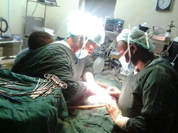 See this viral photo of a doctor with her child on her back performing a cesarean section to save a mother and a baby