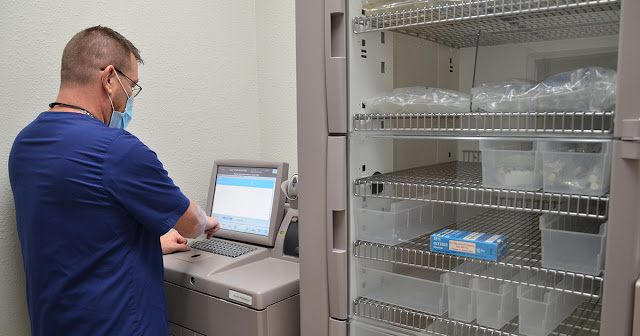 Instructor Ron Enos types into a computer console adjacent to a medical storage unit