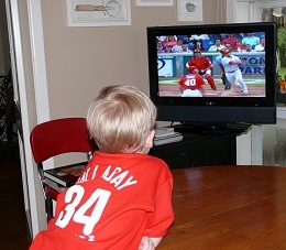 Boy seen from behind in a red Phillies jersey watching baseball on TV