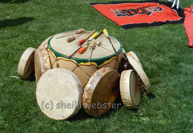 Several drums sit on the grass with tools