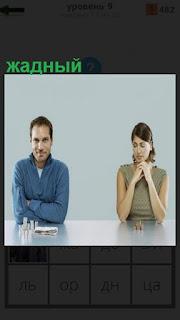 За столом жадный мужчина и женщина руками держится за шею