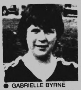 Black and white image of the head and shoulders of a smiling woman in a football kit