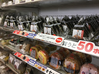 Two shelves of rice-balls, both triangular and round, in a local 7-Eleven