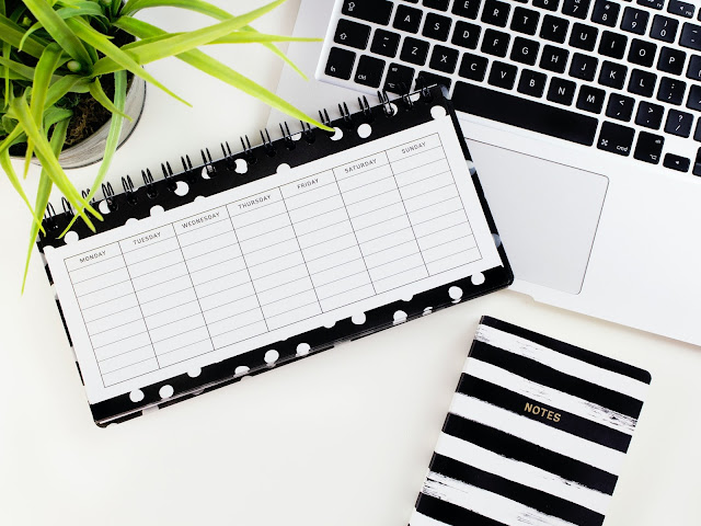 The image shows a black and white polka dot weekly planner on a white desk. Next to the planner is a black and white stripped notebook. The notebook is resting on a laptop's keyboard