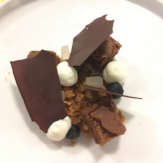 Brownie, espuma de chocolate blanco, arándonos y láminas de chocolate.