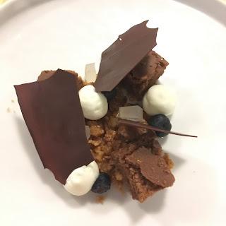 Brownie, espuma de chocolate blanco, arándonos y láminas de chocolate.