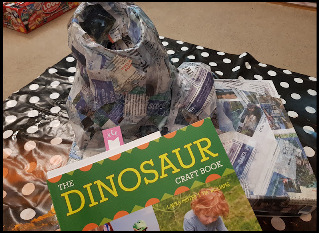 Following the steps in the Dinosaur Craft Book on how to make a volcano