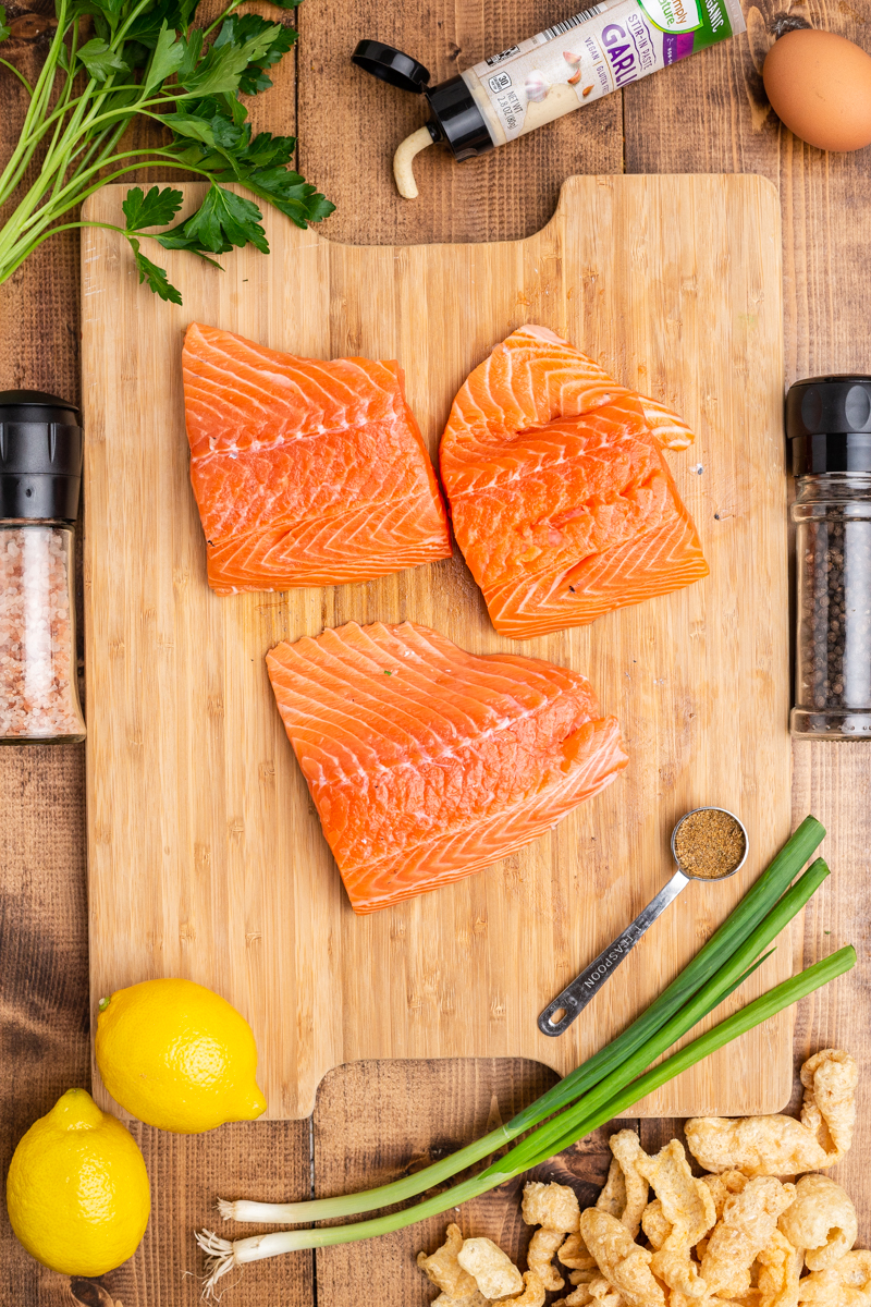 Overhead photo of the ingredients needed to make Keto Salmon Cakes (Salmon Patties) on a wooden table.