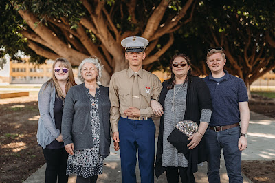 Marine posing with family for photo after graduation boot camp from MCRD SD