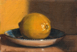 Oil painting of a lemon on a blue and white porcelain saucer.