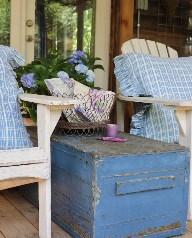 Rustic blue box on back porch shows paint flaked off to bare wood on all sides and top