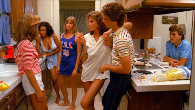 The Slumber Party Massacre 1982 movie still where Michelle Michaels, Debra de Liso, Andree Honore, and Robin Stille stand around in a kitchen