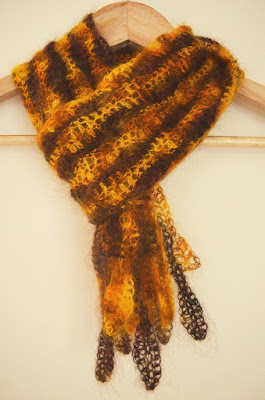 Woodlands Scarf: wavy stripes in gold and brown tones hanging on coathanger as if it were around the neck. The fringe is made of interlocking gold and brown leaf motifs.