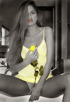 Photo of sexy girl sitting with legs slightly open. Wearing a yellow night gown and holding a yellow rose.