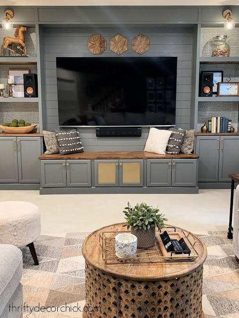 gray basement entertainment center with bench
