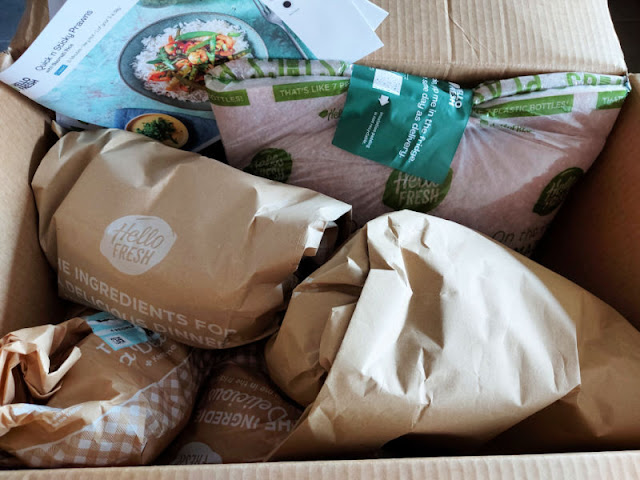 Brown paper bags containing meals in the Hello Fresh delivery.  There are also recipe cards