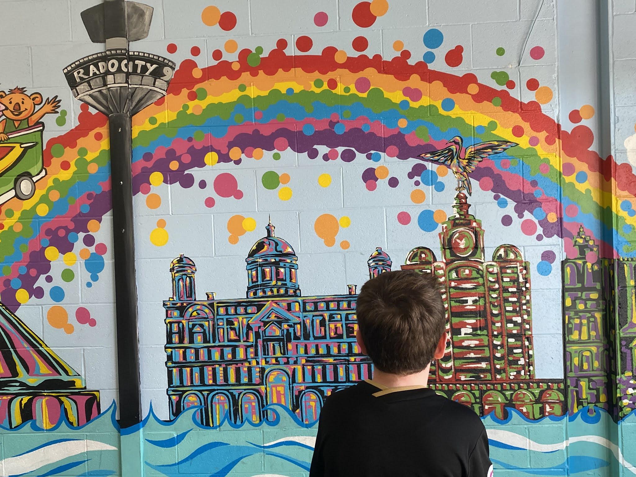 Boy looking at a wall mural