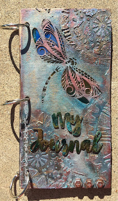 Chipboard journal with a debossed patterned dragonfly cut out colored in greys, blues & burgandy.