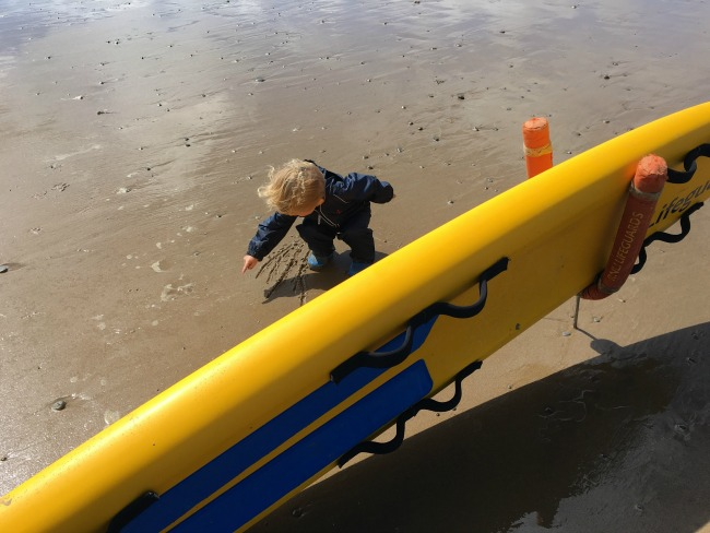 toddler-drawing-lines-in-wet-sand-next-to-a-lifeguards-surf-board