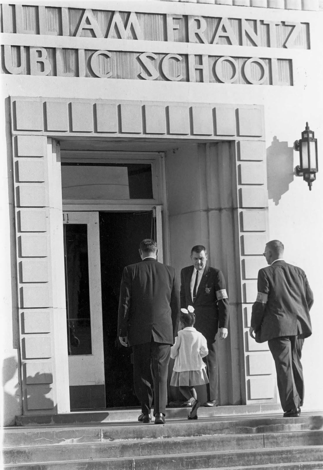 Guarded by three Deputy U.S. Marshals, including Charles Burks, top center, young Ruby Bridges enters newly integrated William Frantz school in New Orleans, La. on Dec. 5, 1960 to begin her third week as the only black student in the school.