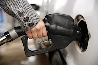 A woman pumps gas at a station in Falls Church, Virginia December 16, 2014. (Credit: Reuters/Kevin Lamarque) Click to Enlarge.