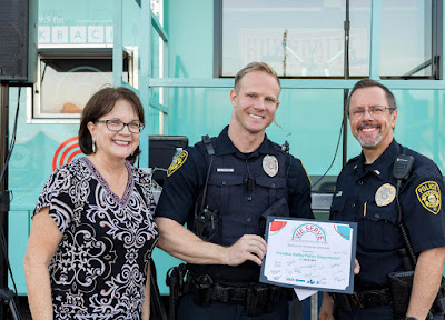 Linda Pastori and police officers Steven McGhee & Michael Cole standing in front of Soundbite truck holding up a certificate of participation.