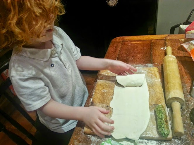 Four year old cooking making a sausage roll