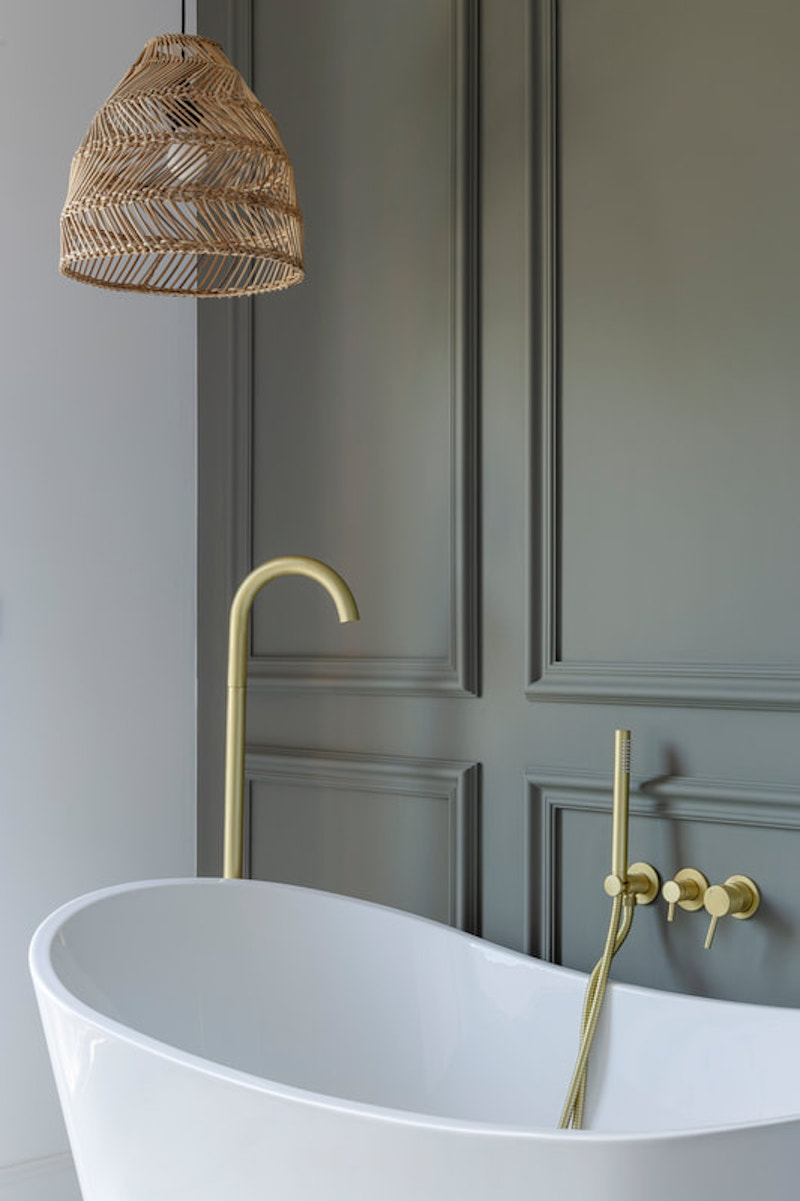 Baño con bañera exenta y pared con escayola decorativa