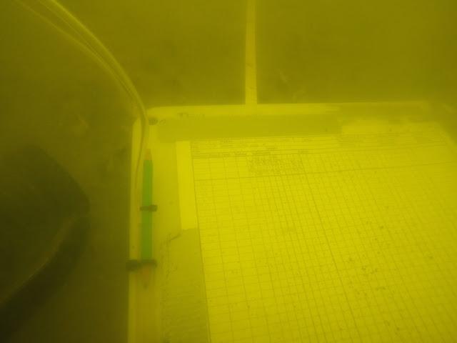 Veden alla otetussa kuvassa on mutaiselle pohjalle laskettu sukeltajan käyttämä kirjoitusalusta, johon on teipattu kiinni sukelluslinjaprotokola. Kirjoitusalustan vieressä on sukelluslamppu, ja kuvan ylälaidassa näkyy sukelluslinjaa merkitsevä pohjaan vedetty mittanauha..
