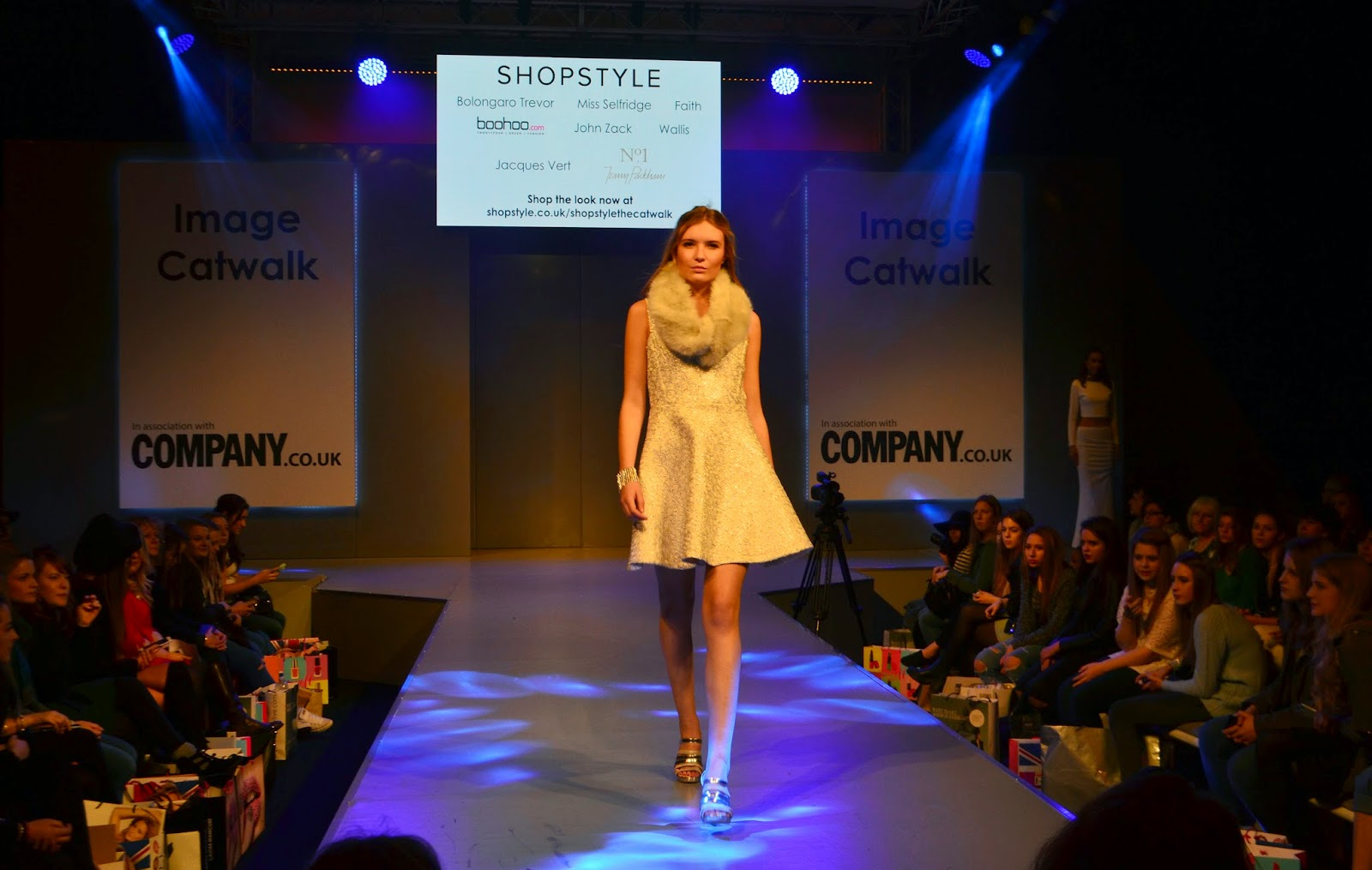 a single model walking down the runway wearing a white dress, silver heels, and a fur snood