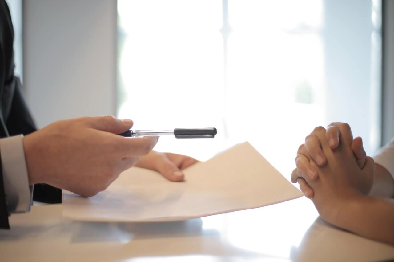 Guy handing pen over to sign
