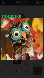 сделана поделка из шишки в виде совы