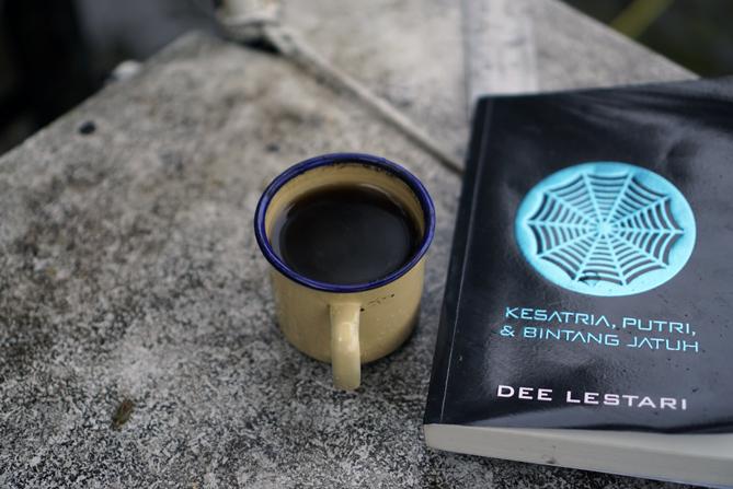 Membaca buku dan menyesap kopi