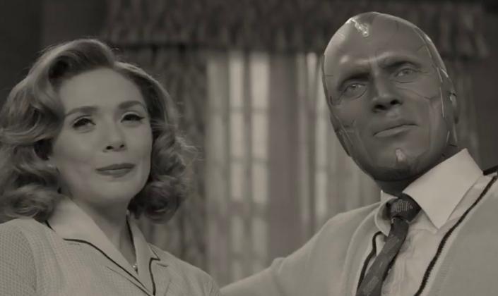 Imagem de capa: Wanda interpretada por Elizabeth Olsen e Visão, interpretado por Paul Bethany, com o rosto metálico, sem cabelos de andróide, em roupas de época dos anos 50 e em preto e branco, sentados um do lado do outro, com o fundo que parece ser as cortinas de uma casa de subúrbio.