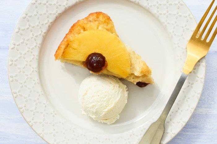A slice of vegan pinepple upside down cake with a scoop of vegan vanilla ice cream