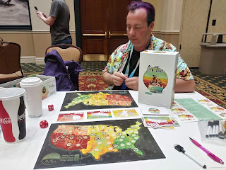 John sitting across the table from me as we play a game called On Tour. The box is standing up to be clearly visible. Each of us has a dry-erase board marked with a map of the continental United States. Some of the states have numbers written on them. A set of cards sits nearby, with three dealt out in the middle of the table, each one showing a region of the nation, with a state in that region marked. Two ten-sided dice sit nearby.